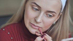 Menina loura para aplicar o batom com o lápis cosmético nos bordos vídeos de arquivo