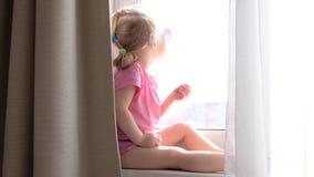 Menina loura pequena bonito em óculos de sol cor-de-rosa que bebe seu café ou chá da manhã pela janela, olhando fora vídeos de arquivo