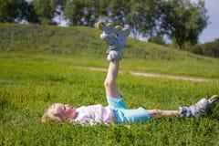 Menina loura pequena bonito que senta-se na grama verde e que põe sobre patins de rolo - lazer, infância, jogos exteriores e conc fotografia de stock royalty free