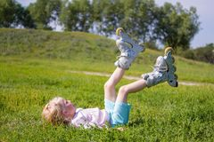 Menina loura pequena bonito que senta-se na grama verde e que põe sobre patins de rolo - lazer, infância, jogos exteriores e conc foto de stock royalty free