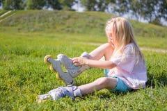 Menina loura pequena bonito que senta-se na grama verde e que põe sobre patins de rolo - lazer, infância, jogos exteriores e conc imagem de stock