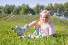 Menina loura pequena bonito que senta-se na grama verde em patins de rolo e que olha a câmera - lazer, infância, jogos exteriores foto de stock