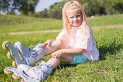 Menina loura pequena bonito que senta-se na grama verde em patins de rolo e que olha a câmera - lazer, infância, jogos exteriores foto de stock royalty free