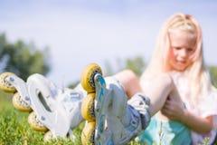 Menina loura pequena bonito que senta-se na grama verde em patins de rolo foco seletivo - lazer, infância, jogos exteriores e eng foto de stock royalty free