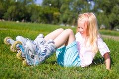 Menina loura pequena bonito que senta-se na grama verde no lazer dos patins de rolo, na infância, em jogos exteriores e em concei fotos de stock