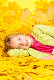 A menina loura pequena coloca nas folhas do amarelo do outono Fotos de Stock