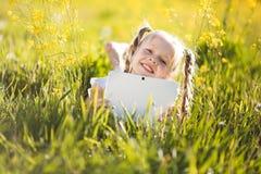 Menina loura pequena com a tabuleta digital na natureza fotografia de stock