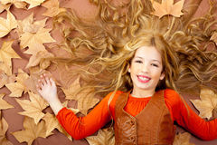A menina loura pequena da queda do outono na árvore secada sae Imagens de Stock Royalty Free