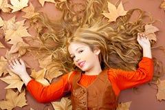 A menina loura pequena da queda do outono na árvore secada sae Fotografia de Stock Royalty Free