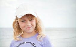 Menina loura pequena de sorriso na costa de mar Fotos de Stock Royalty Free