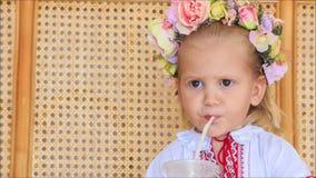 Menina loura pequena do close up em Garland Drinks Juice filme