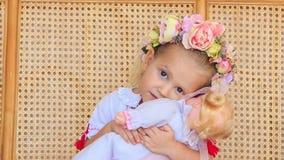 Menina loura pequena do close up em Garland Sits com boneca filme