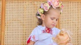 Menina loura pequena do close up em Garland Sits com boneca video estoque