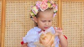 Menina loura pequena do close up em Garland Sits com boneca vídeos de arquivo