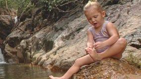 A menina loura pequena do close up limpa o pé na pedra pelo rio video estoque
