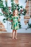 Menina loura pequena em um vestido brilhante em uma sala decorada com flores Foto de Stock