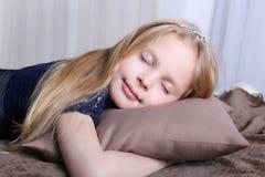 A menina loura pequena está dormindo em um descanso Fotografia de Stock