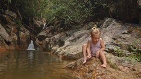 A menina loura pequena limpa os dedos do pé levanta-se pela cachoeira vídeos de arquivo