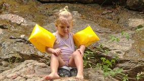 A menina loura pequena nas Braço-mãos senta o pé dos riscos na pedra filme