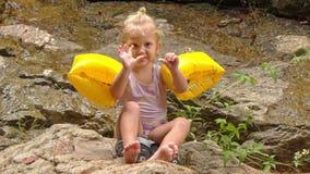 A menina loura pequena nas Braço-mãos senta os pés dos toques na pedra vídeos de arquivo