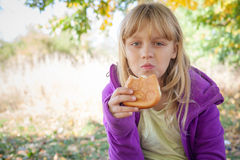 A menina loura pequena no parque come a torta pequena Imagens de Stock