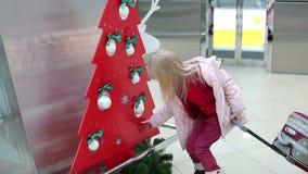 Menina loura pequena no revestimento do inverno com mala de viagem que anda através do salão de espera no aeroporto vídeos de arquivo