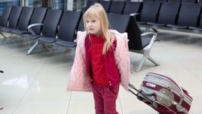 Menina loura pequena no revestimento do inverno com a mala de viagem que espera através do salão de espera no aeroporto filme