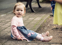 Menina loura pequena no vestido bonito que senta-se na terra Imagens de Stock