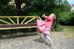 Menina loura pequena que está com mãos levantadas entre as pétalas da flor da árvore na terra Fotografia de Stock