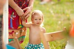 A menina loura pequena que está na grama Fotografia de Stock