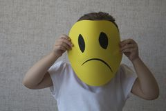 Menina loura pequena que guarda as máscaraes protetoras tristes que simbolizam emoções em mudança Foto de Stock Royalty Free