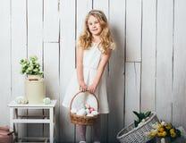 Menina loura pequena que guarda a cesta com ovos pintados Dia da Páscoa Foto de Stock Royalty Free