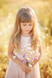 Menina loura pequena que olha o ramalhete Fotografia de Stock