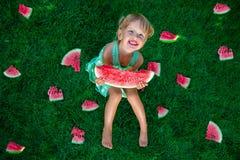 Menina loura pequena que senta na grama em torno do fatias de melancia no verão feliz Fotos de Stock