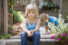 Menina loura pequena que senta-se em etapas Foto de Stock Royalty Free