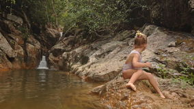 A menina loura pequena senta-se no pai de pedra Puts em Panamá pelo rio video estoque