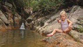A menina loura pequena senta-se pede o fruto na pedra pela cachoeira filme