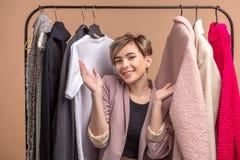 A menina loura positiva com braços aumentados está convidando clientes imagem de stock royalty free