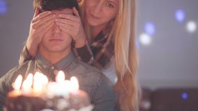 A menina loura que cobre os olhos do homem, a seguir deixou-o ver o bolo com muitas velas O indivíduo tem a celebração do anivers video estoque