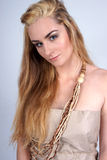 Menina loura que desgasta grânulos e o vestido de madeira do papel Imagens de Stock Royalty Free