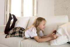 Menina loura que encontra-se no sofá home do sofá usando o Internet app na almofada digital da tabuleta na almofada digital da ta Foto de Stock