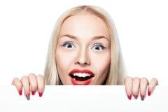 Menina loura que espreita para fora atrás do cartaz. Imagem de Stock Royalty Free