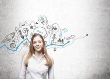 Menina loura que está perto dos ícones startup azuis e pretos Imagem de Stock