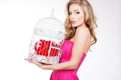 Menina loura que guarda a gaiola branca com coração vermelho Foto de Stock Royalty Free