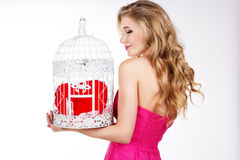 Menina loura que guarda a gaiola branca com coração vermelho Fotografia de Stock Royalty Free