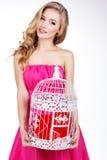 Menina loura que guarda a gaiola branca com coração vermelho Imagens de Stock Royalty Free
