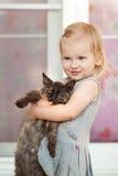 Menina loura que guarda um gato Imagem de Stock