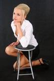 Menina loura que inclina-se em uma cadeira Foto de Stock Royalty Free