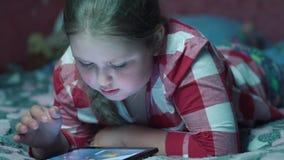 Menina loura que joga o jogo na tabuleta e que encontra-se no sofá na noite 4K video estoque