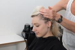 Menina loura que obtém uma massagem principal na loja de um cabeleireiro Imagens de Stock